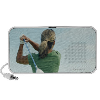 Young woman swinging golf club, rear view mini speakers