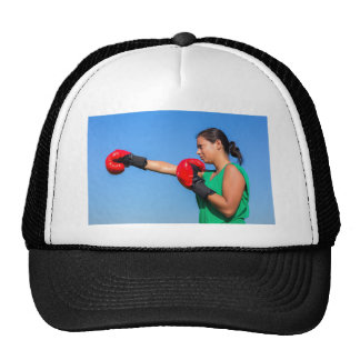 Young woman wearing red boxing gloves blue sky cap
