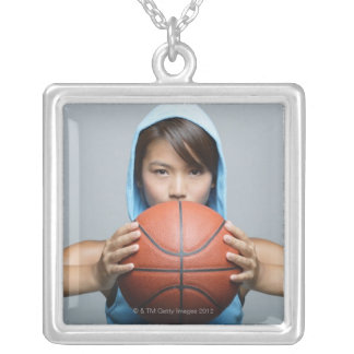 Young woman with basketball looking at camera silver plated necklace